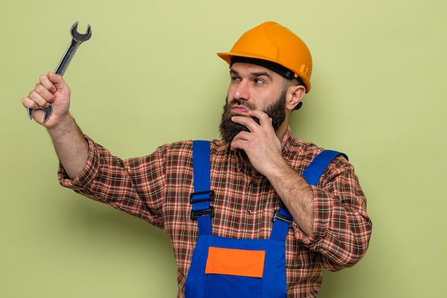 Constructeur barbu en uniforme de construction et casque de sécurité tenant une clé le regardant intrigué debout sur fond vert