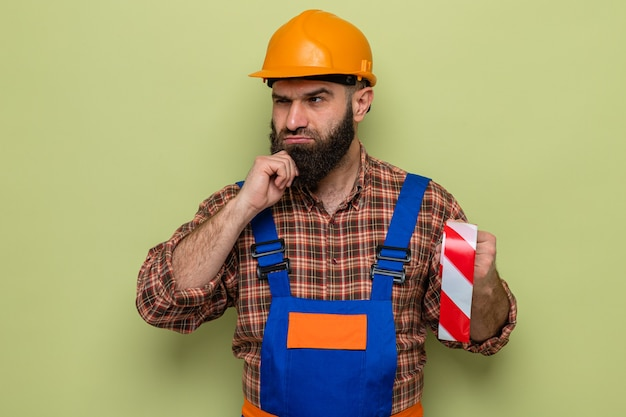 Constructeur barbu en uniforme de construction et casque de sécurité tenant du ruban adhésif regardant de côté avec une expression pensive sur la pensée du visage