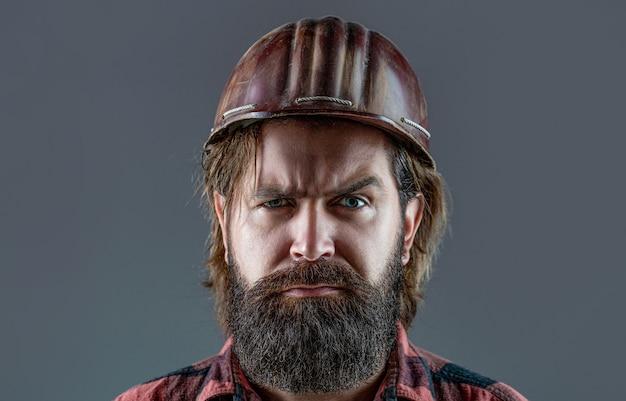 Constructeur en casque, contremaître ou réparateur dans le casque. bâtiment, industrie - concept de constructeur. travailleur barbu avec barbe dans un casque de construction ou un casque. constructeurs d'hommes, industrie