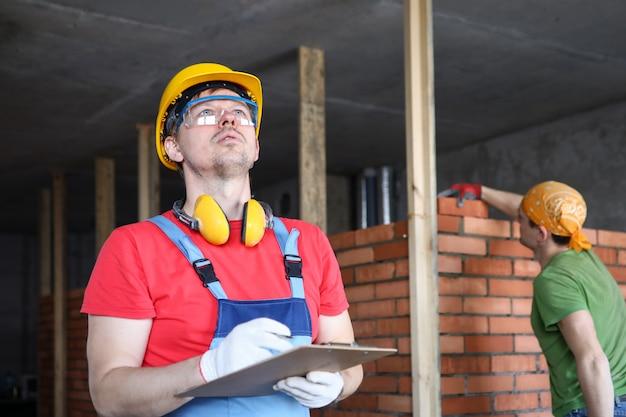 Le constructeur en combinaison et casque prend des notes sur un presse-papiers.