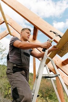 Constructeur construisant le toit de la maison