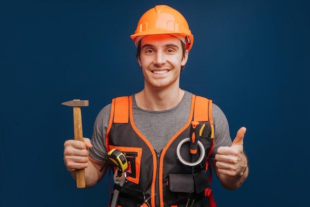 Constructeur dans un casque avec un marteau sourit et abandonne le pouce