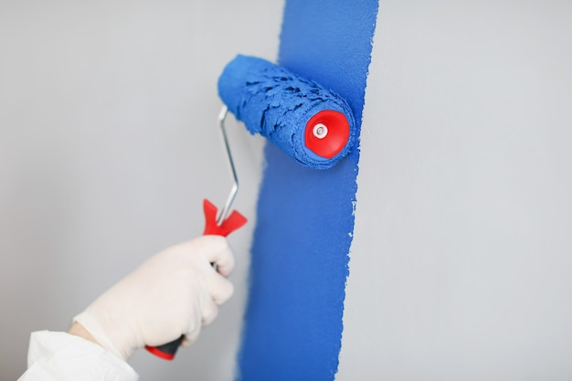 Constructeur dans des gants de protection peignant le mur blanc bleu avec le plan rapproché de rouleau