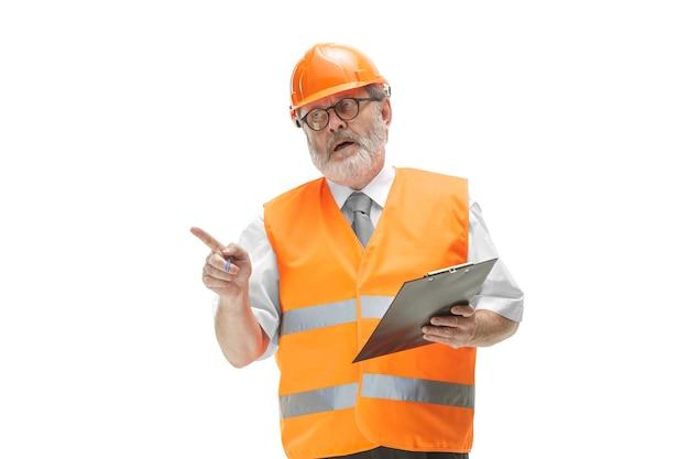 Le constructeur dans un gilet de construction et un casque orange debout sur blanc.