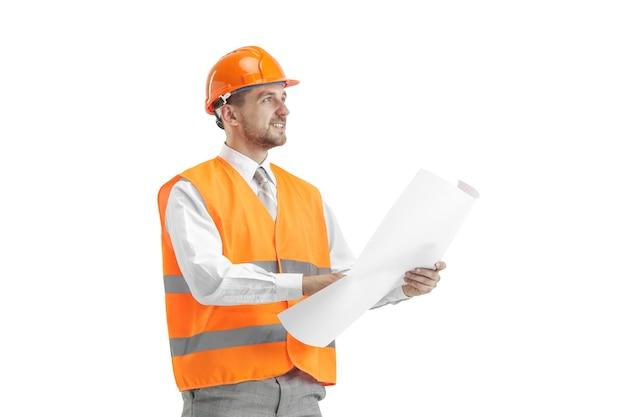 Le constructeur dans un gilet de construction et un casque orange debout sur un mur blanc. spécialiste de la sécurité, ingénieur, industrie, architecture, gestionnaire, profession, homme d'affaires, concept d'emploi