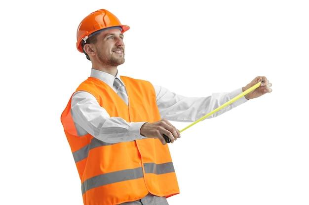 Le constructeur dans un gilet de construction et casque orange debout sur studio blanc