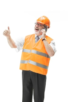 Le constructeur dans un gilet de construction et un casque orange parle sur un téléphone portable de quelque chose.