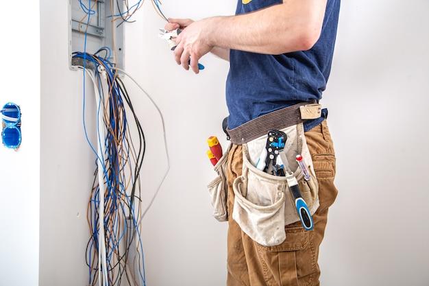 Constructeur électricien au travail, examine la connexion du câble dans la ligne électrique dans le fuselage d'un tableau industriel. professionnel en salopette avec un outil d'électricien.