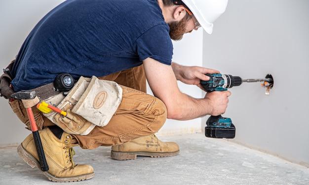 Constructeur électricien au travail, installation de lampes en hauteur. professionnel en salopette avec une perceuse. le concept de travail en tant que professionnel.