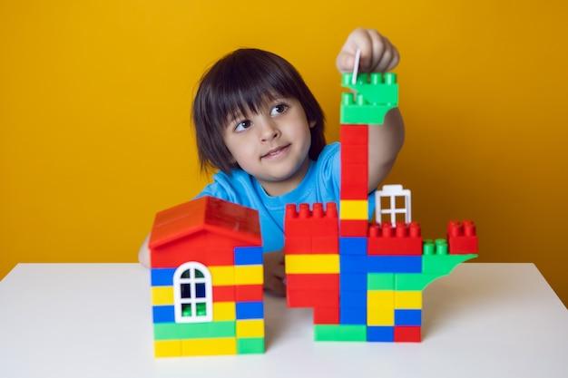 Constructeur d'enfant garçon dans un t-shirt bleu contre un mur jaune construit une maison à partir de cubes en plastique colorés.