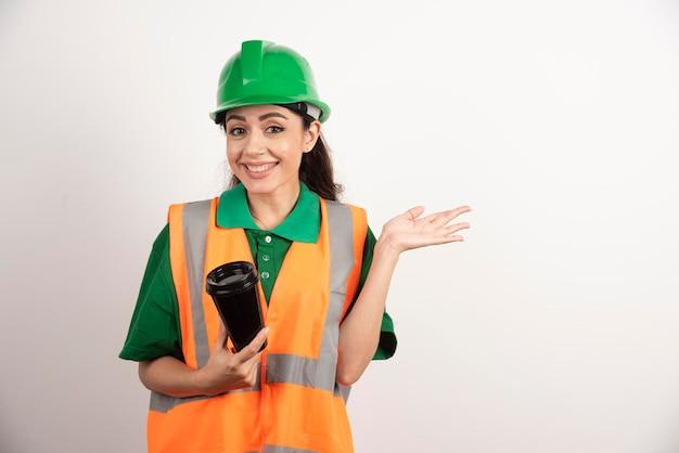 Constructeur féminin souriant avec une tasse noire. photo de haute qualité