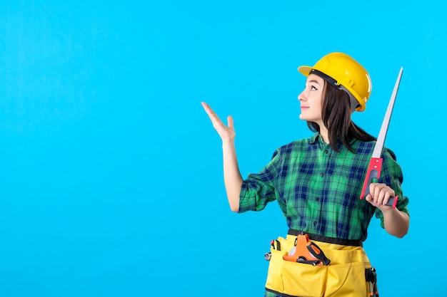 Constructeur féminin de vue de face tenant la petite scie sur le bleu