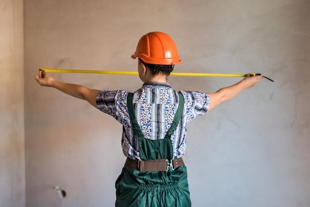 Constructeur de femme en mur de mesure uniforme avec du ruban adhésif