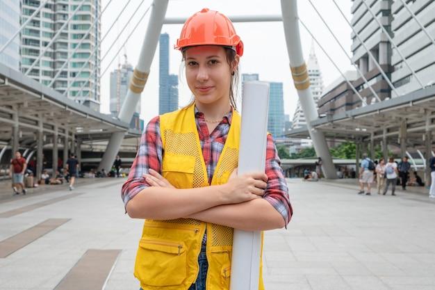 Constructeur de femme de race blanche en gilet de sécurité avec casque bras croisés et tenant la disposition du site de construction dans l'urbain