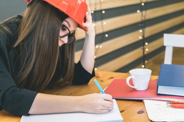 Constructeur de femme réfléchie écrivant quelque chose