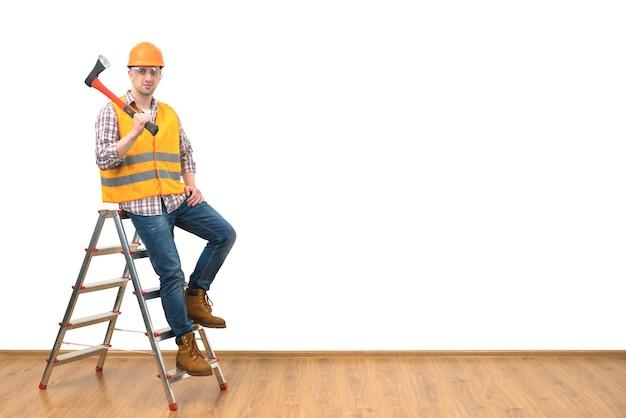 Le constructeur avec la hache se tenant sur l'échelle sur le fond blanc de mur
