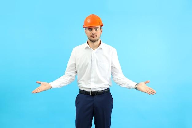 Constructeur d'homme d'affaires dans l'incompréhension sur fond bleu.