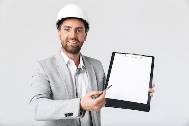 Constructeur d'homme barbu confiant portant un costume et un casque debout isolé sur un mur blanc, montrant un bloc-notes vierge