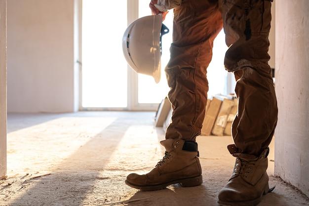 Un constructeur d'homme avec un casque dans ses mains copiez l'espace