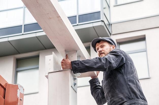 Un constructeur d'homme fort dans une combinaison de construction sombre et une casquette construit une maison dans la rue à partir du bois