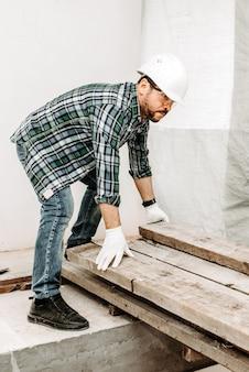 Le constructeur de l'homme réorganise les poutres en bois au chantier de construction