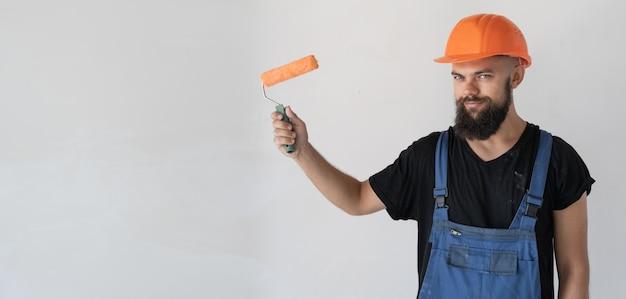 Un constructeur d'hommes est vêtu de vêtements spéciaux et un casque orange se tient près d'un mur blanc. tenir un rouleau à peinture. espace de copie