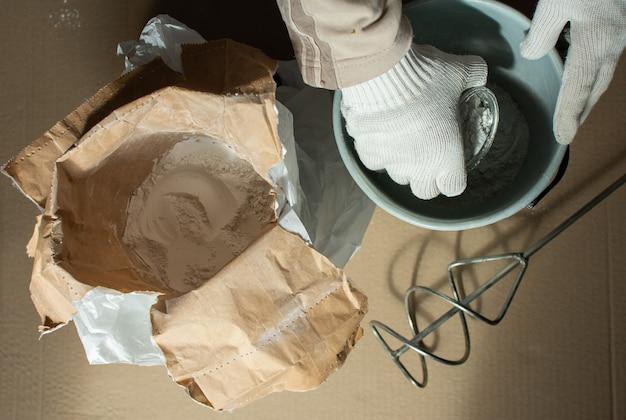 Le constructeur d'hommes prépare un mélange pour le mastic, le sac avec le mastic de gypse et le mélangeur de perceuse