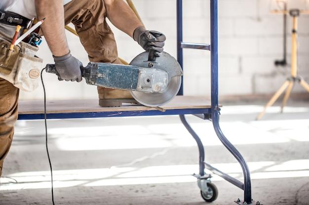 Le constructeur industriel travaille avec une meuleuse d'angle professionnelle pour couper des briques et construire un mur intérieur