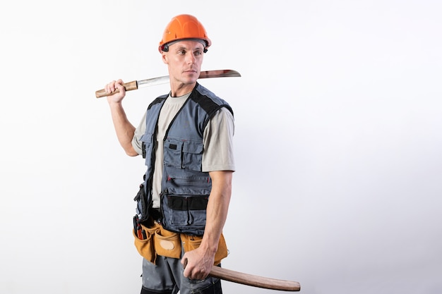 Un constructeur avec un katana court dans une main et une gaine dans l'autre. réparateur portant un casque et des vêtements de travail.pour tout usage.