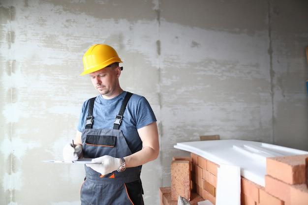 Constructeur masculin dans un casque jaune détient
