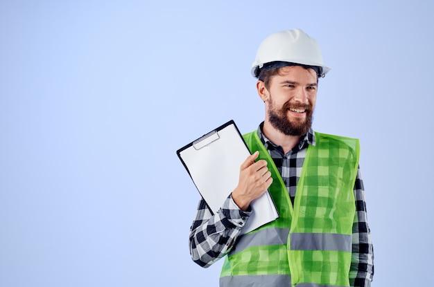 Constructeur masculin dans un fond bleu de conception de travaux de vestconstruction vert. photo de haute qualité
