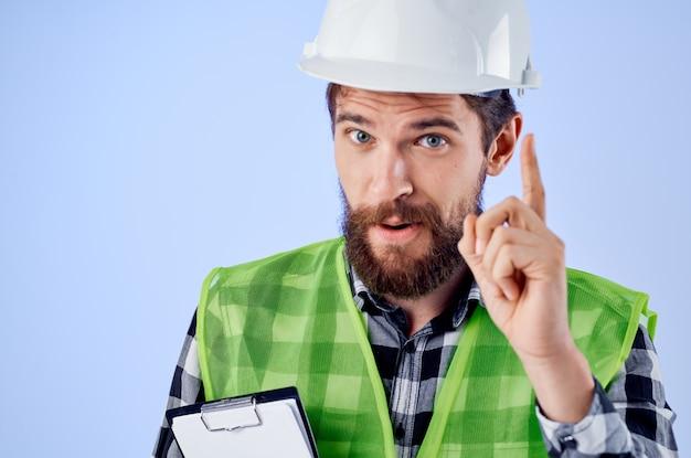Constructeur masculin dans un fond bleu de conception de travaux de vestconstruction vert