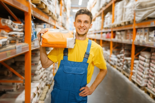 Le constructeur masculin détient un sac de ciment dans une quincaillerie constructeur en uniforme regarde les marchandises dans la boutique de bricolage