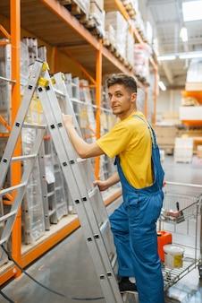 Constructeur masculin monter les escaliers en quincaillerie. constructeur en uniforme regarde les marchandises dans la boutique de bricolage