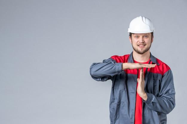 Constructeur masculin vue de face en uniforme et casque sur fond clair