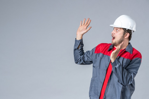Constructeur masculin vue de face en uniforme et casque sur fond gris