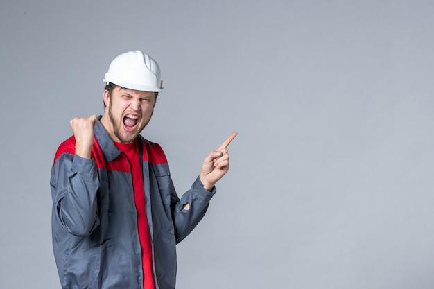 Constructeur masculin vue de face en uniforme se réjouissant émotionnellement sur fond clair
