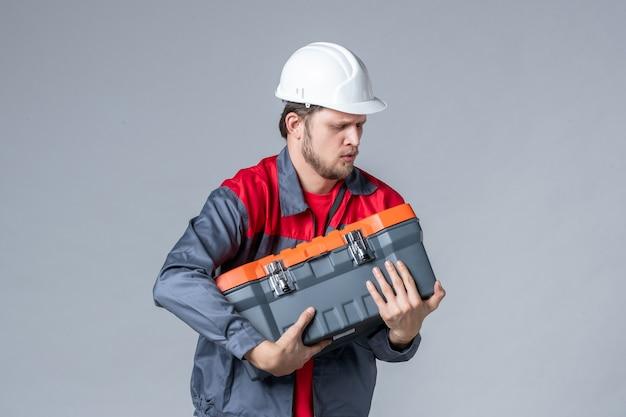 Constructeur masculin vue de face en uniforme tenant une mallette à outils lourde sur fond gris