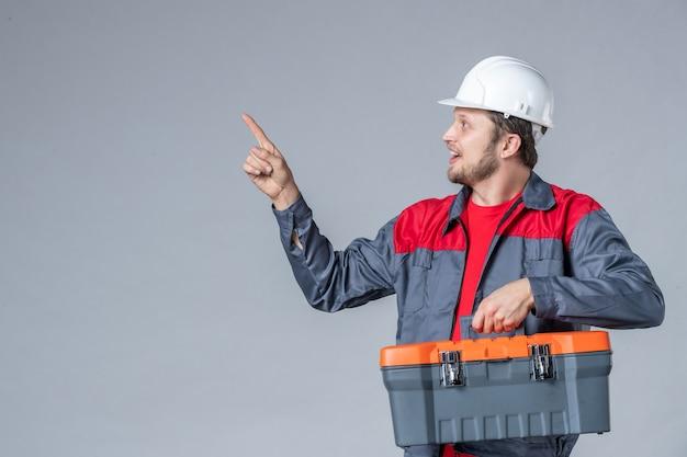 Constructeur masculin vue de face en uniforme tenant une trousse à outils sur fond gris