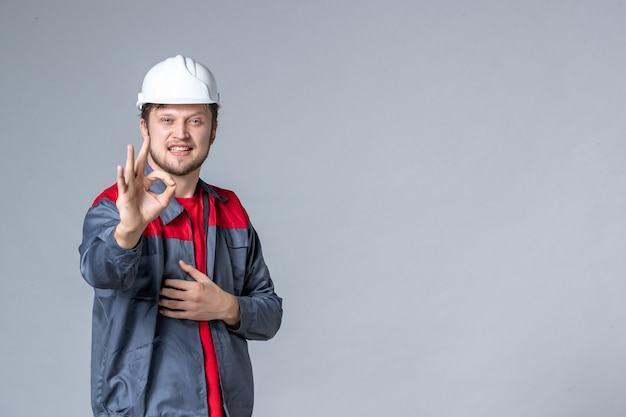 Constructeur masculin vue de face en uniforme avec un visage ravi sur fond clair