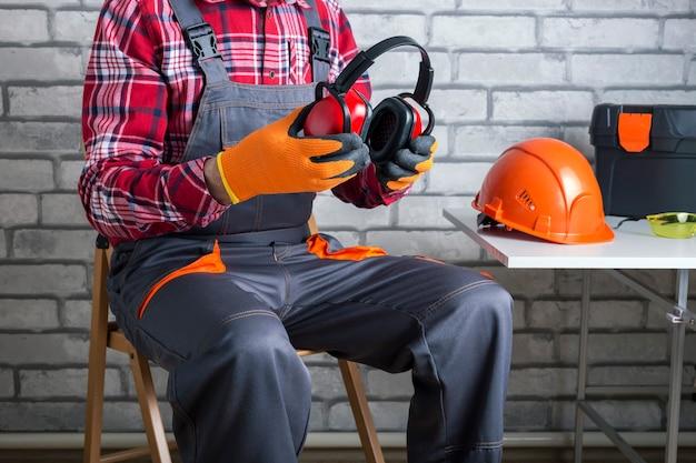 Le constructeur met un équipement de protection individuelle. travailleur manuel mettant des écouteurs de protection.