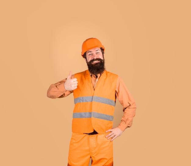Le constructeur montre le pouce vers le haut du travailleur de la construction dans le constructeur de concept de l'industrie du bâtiment d'entreprise de casque de sécurité dans
