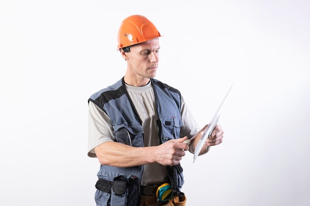 Le constructeur nettoie une spatule dans des vêtements de travail et un casque sur un fond gris clair