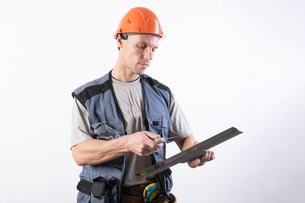 Le constructeur nettoie une spatule. en tenue de travail et casque. sur un fond gris clair. pour n'importe quel but.