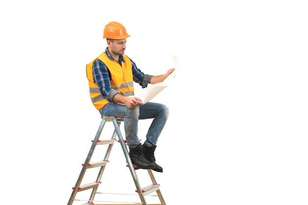 Le constructeur avec un papier assis sur l'échelle sur fond blanc