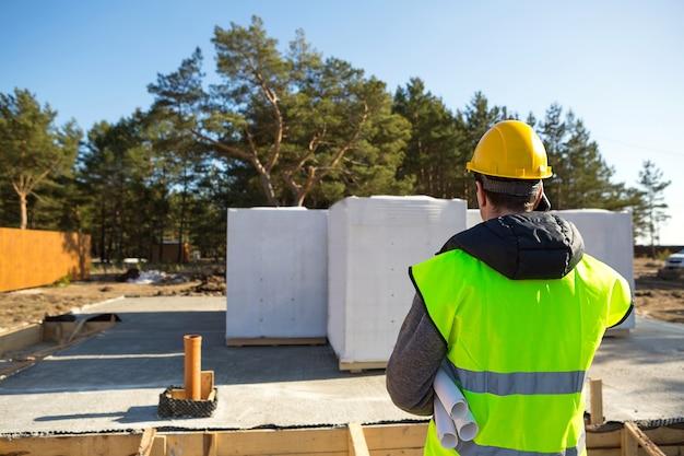 Le constructeur parle au téléphone. architecte dans un casque de protection jaune et un gilet de signalisation se tient en arrière devant le chantier de construction