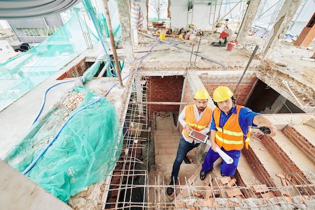 Le constructeur parle à l'entrepreneur et lui montre les murs finis dans un bâtiment en construction