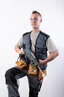 Constructeur avec une perceuse dans ses mains, dans des lunettes de sécurité. pour n'importe quel but.