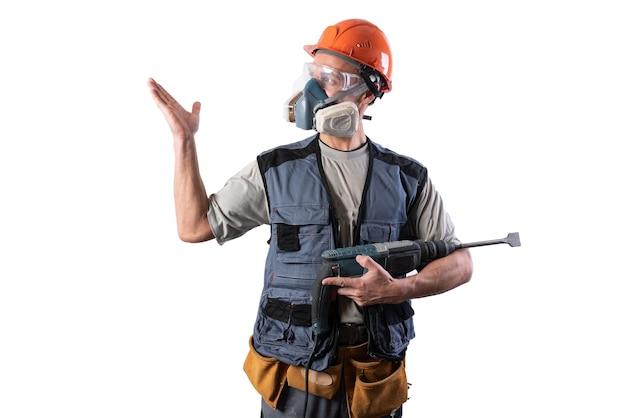 Le constructeur avec la perceuse perforatrice, dans un casque, pointe vers la gauche. pour n'importe quel but.