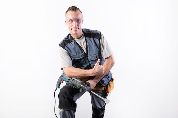 Constructeur avec une perceuse sur son genou, en lunettes de sécurité. pour n'importe quel but.